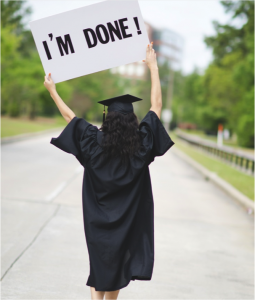 Happy student with im done sign. Wearing high school graduation gowns