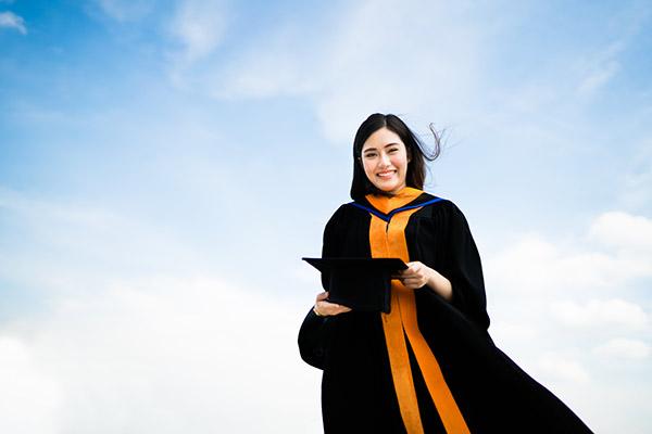Happy graduate wearing her academic regalia in Australia
